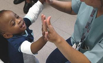 A nurse and a small child double high-fiving