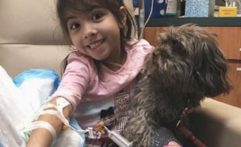 A smiling girl having blood drawn and holding a dog in her lap