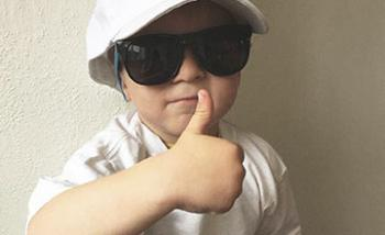 A young boy wearing an oversized cap and sunglasses giving a thumbs up.